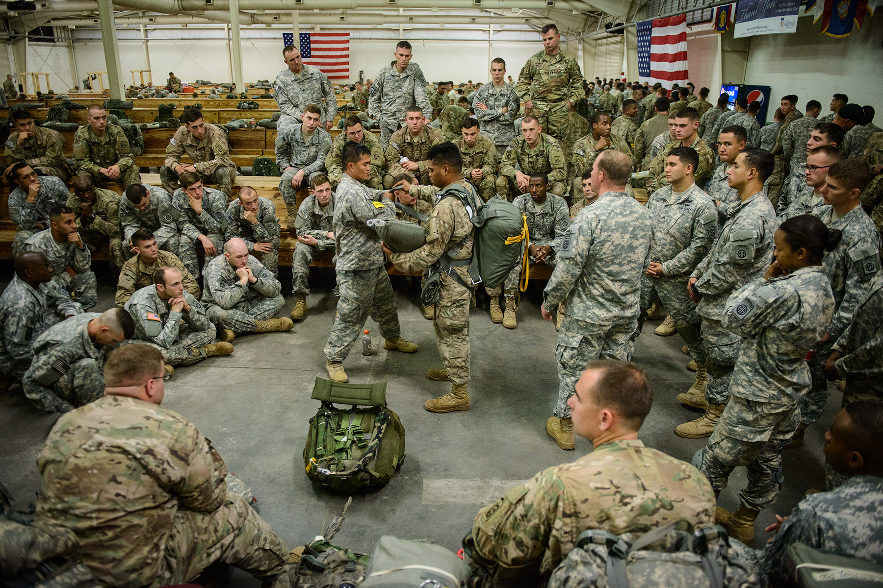 First Place | Multiple PhotosAndrew Craft, The Fayetteville Observer2nd Brigade Combat Team paratroopers watch a demonstration of putting on a proper rig at Green Ramp before heading to Zaragoza, Spain, Tuesday, Nov. 3, 2015, where they will jump in as part of Operation Trident Juncture 15. In support of Operations Trident Juncture 15 and Ultimate Reach 16, over 500 Paratroopers from the Division's 2nd Brigade Combat Team deployed from Pope Army Airfield, conducted in-flight rigging and executed a Joint Forcible Entry exercise in Zaragoza, Spain.