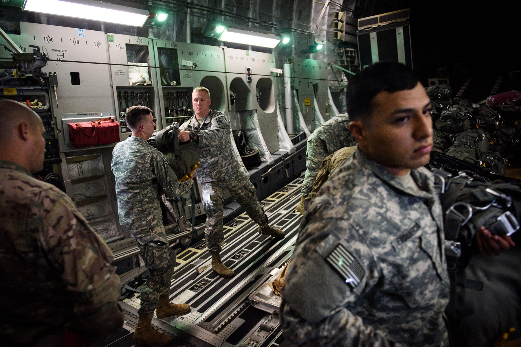First Place | Multiple PhotosAndrew Craft, The Fayetteville ObserverParachutes are handed out to paratroopers for in flight rigging as they head for Zaragoza, Spain, Wednesday, Nov. 4, 2015, where they will jump in as part of Operation Trident Juncture 15. In support of Operations Trident Juncture 15 and Ultimate Reach 16, over 500 Paratroopers from the Division's 2nd Brigade Combat Team deployed from Pope Army Airfield, conducted in-flight rigging and executed a Joint Forcible Entry exercise in Zaragoza, Spain.