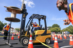 Honorable Mention I FeatureAileen Devlin, Aileen DevlinOverton's Allen Denton, center, attempts to place a wooden spool onto a metal rod as volunteer Mike Carmon, right, watches for a mistake during Pitt Community College's 3rd Annual Forklift Rodeo held in the Greenville Mall parking lot on Friday, Oct. 9, 2015.