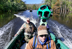 First Place | Multiple PhotosAileen Devlin, Aileen DevlinRoanoke Outdoor Adventure's owner and operator Hebert Coltrain, left, drives the boat along Devil's Gut on the lower end of the Roanoke River in Williamston, N.C. as The Conservation Firm's Justin Boner, center, wears the Google Trekker device as they film the area assisting Google to create a virtual adventure on Monday, Oct. 19, 2015.