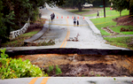 Third Place | Multiple PhotosMykal McEldowney, The Greenville NewsPeople walk up to see a piece of the road near Eastshore Road  that washed away in Columbia on Oct. 5, 2015.
