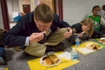 Third Place | Multiple PhotosSara Corce, The PilotMoore County School Superintendent Bob Grimesey takes a bite from his Thanksgiving style school lunch as he sits with members of the first grade class at Vass-Lakeview Elementary School on Tuesday, November 24, 2015 in Vass, North Carolina.