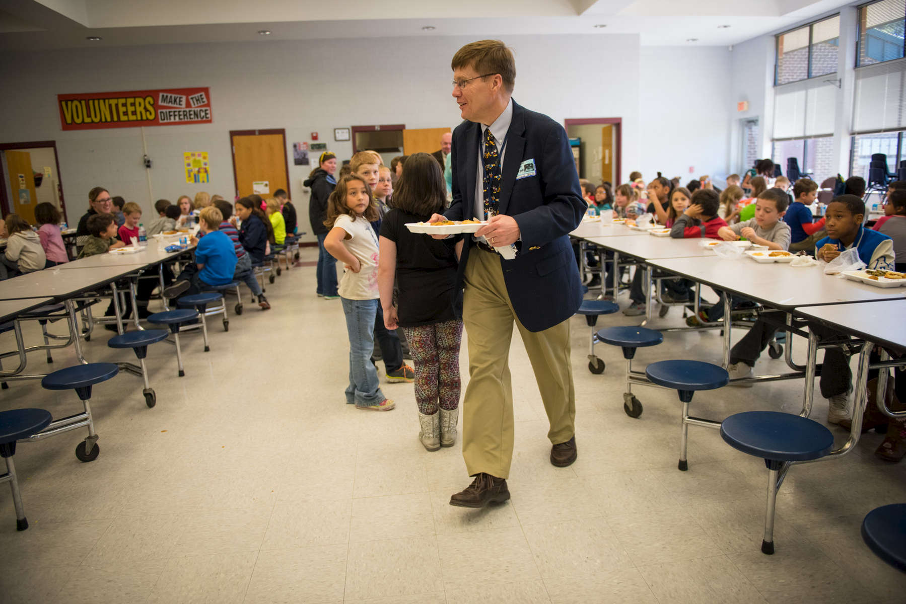 Third Place | Multiple PhotosSara Corce, The PilotMoore County School Superintendent Bob Grimesey walks to a lunch table in the cafeteria as he spends time with students on Tuesday, November 24, 2015 at Vass-Lakeview Elementary School in Vass, North Carolina.
