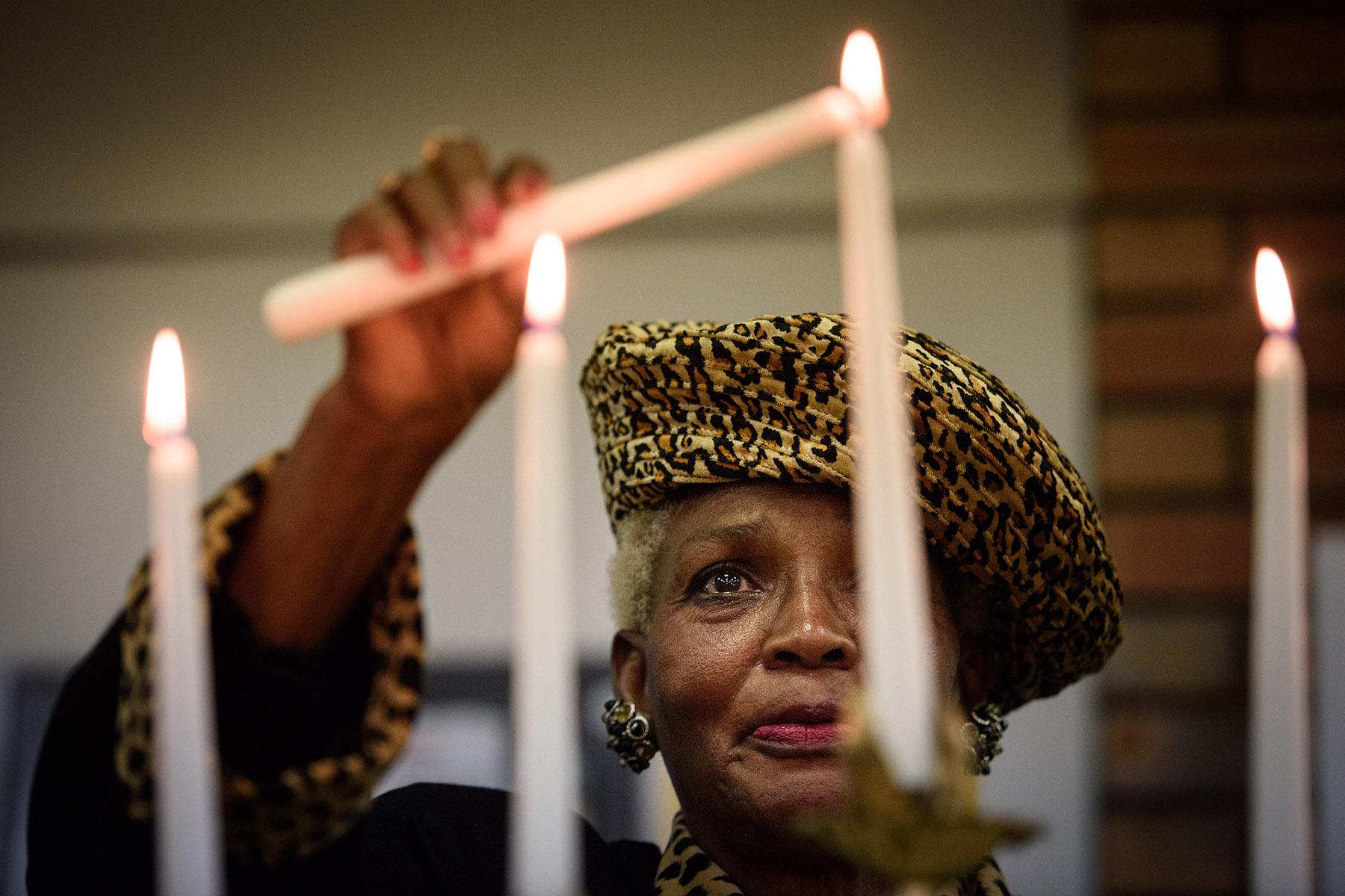 First Place | General News Andrew Craft, The Fayetteville Observer Louise McQueen lights the memorial candles at the Fayetteville/Cumberland County Dr. Martin L. King Jr. Committee Candlelight Service on Thursday, Jan. 14, 2016, at the Senior Citizens Service Center on Blue Street.