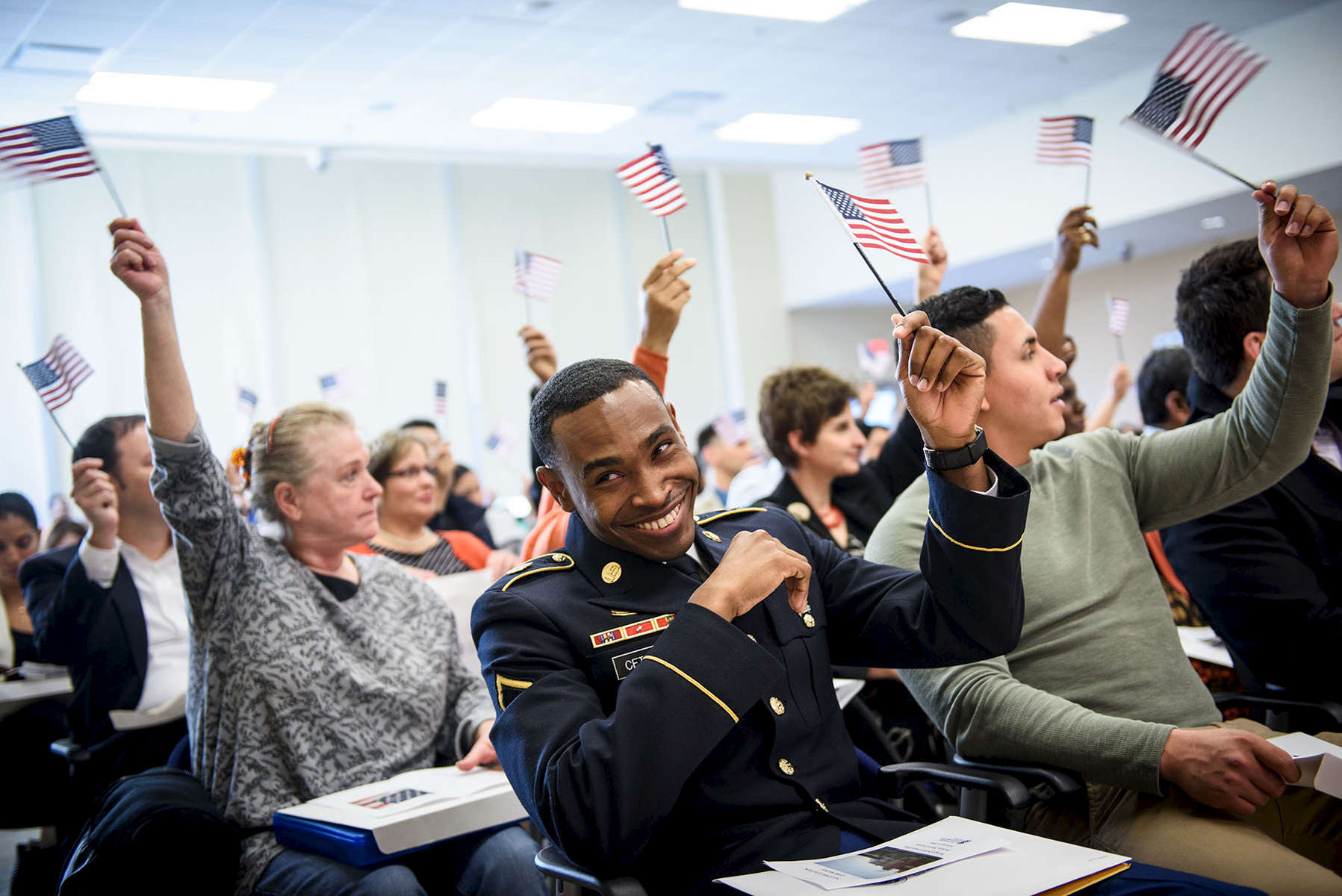 First Place | FeatureAndrew Craft, The Fayetteville ObserverPvt. Mookerdjee Cetoute waves an American flag along with 60 other candidates during a naturalization ceremony on Friday, Feb. 5, 2016, at the U.S. Citizenship and Immigration Services Raleigh-Durham Field Office.