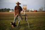 Second Place | PortraitEamon Queeney, North State JournalPainter Fen Rascoe poses for a photograph with his 8-year-old Jack Russell and Mountain Feist mix, Gus, and a recently completed plein air painting of a farm near Mount Gould, North Carolina off the banks of the Chowan River, Sunday afternoon, February 21, 2016. Rascoe, who calls Windsor in Bertie County home, has been painting steady for six years in which he refers jokingly as his mid-life crisis. His work is mostly contemporary impressionism with a focus on plein air painting. Gus whom he calls his {quote}de facto assistant,{quote} accompanies the artist on all his paintings in the countryside.