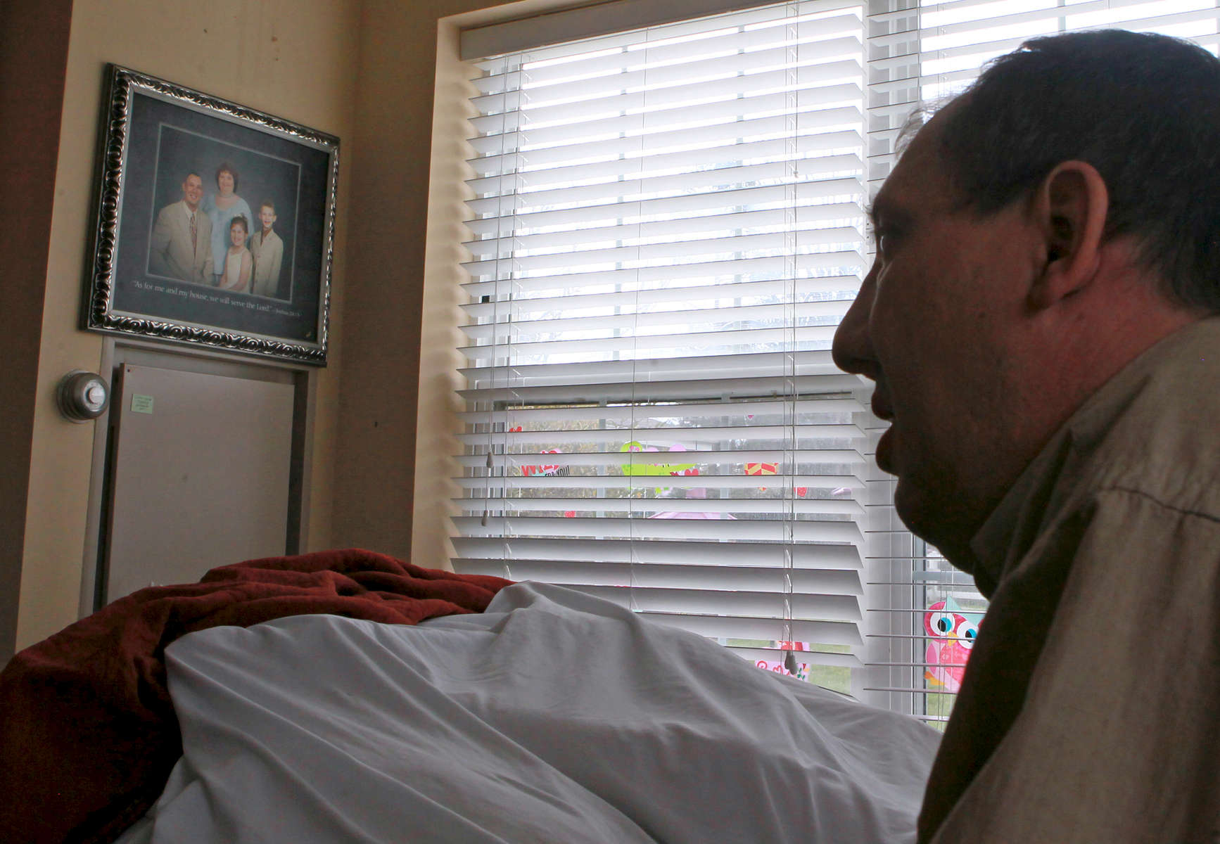 First Place | Multiple PhotosKen Ruinard, Anderson Independent MailRev. Gregg Loner of Honea Path looks at a family portrait with his wife Dee Loner and children hanging in her room at Brookdale Senior Living Solutions in Greenville.
