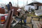 Second Place | Multiple PhotosMark Dolejs, Daily DispatchWill McKenzie (left) and George Hoyle load a piece of furniture into a truck after recovering it from Hoyle's aunt's home on Huntsboro Road. Ann Barnes was at home as a tornado removed part of the roof of her home Wednesday night.