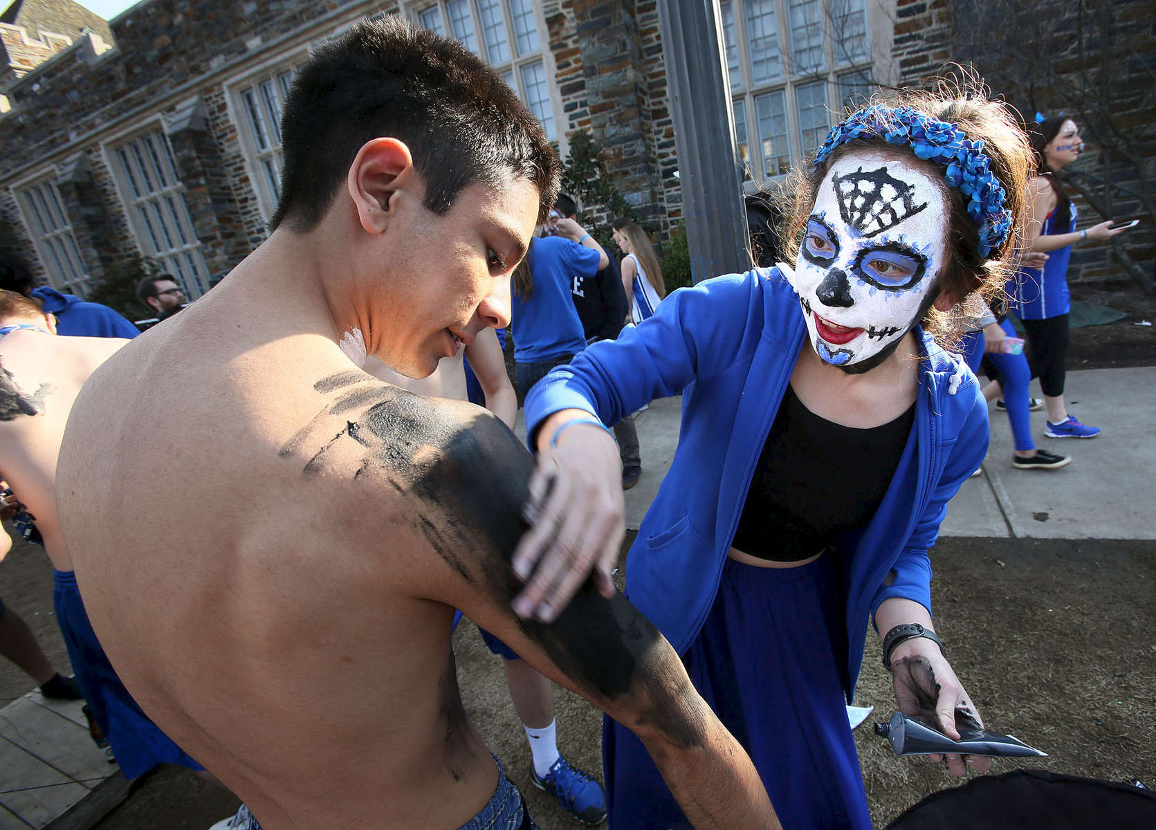 Second Place | Multiple PhotosMark Dolejs, Daily DispatchDuke junior Grace Chang applies paint to sophomore Tavo Loaiza as they wait outside before the start of the Duke Blue Devils and North Carolina Tar Heels college basketball game at Cameron Indoor Stadium.