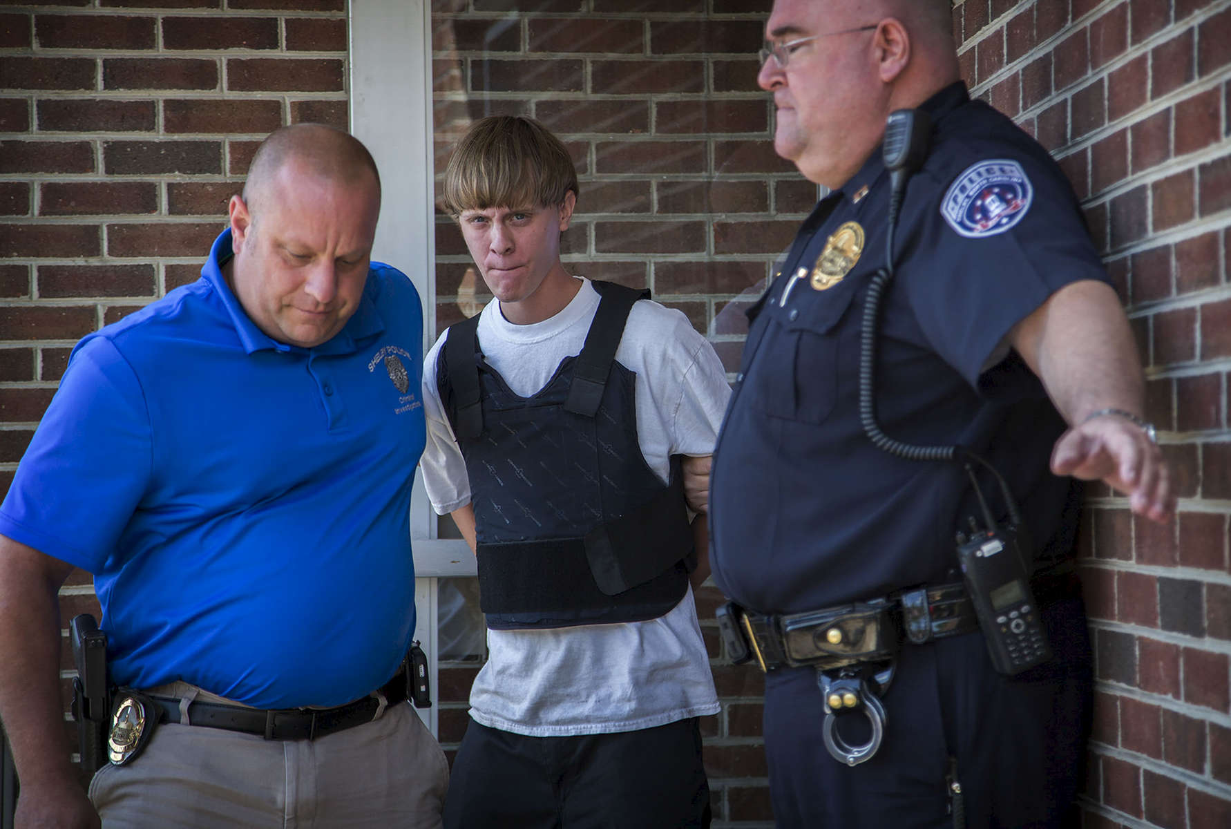 First Place | General News Dillon Deaton, UNC Chapel HillCharleston shooting suspect Dylann Roof is escorted from the Shelby Police Department in Shelby, N.C. on Thursday, June 18, 2015. After a massive manhunt, police apprehended Roof during a traffic strop in Shelby, N.C. after receiving a tip from a motorist. Roof entered Emanuel African Methodist Episcopal Church in Charleston, SC on June 17, 2015 and quietly sat through around an hour of bible study before pulling out a pistol and killing nine people. Joey Meek, a friend of Roof, told The associated Press that Roof had drunkenly complained that {quote}blacks were taking over the world{quote} and {quote}someone needed to do something about it for the white race.{quote} Roof faces state and federal charges including nine murder counts, hate crimes, and obstruction of the practice of religion.