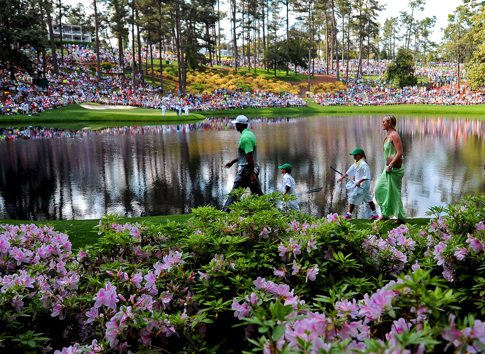 Third Place | Pictorial Jeff Siner, The Charlotte ObserverTiger Woods leads his son, Charlie, daughter, Sam and partner Lindsey Vonn past the azaleas toward the ninth green at Augusta National Golf Club.