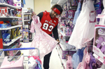Sports POY: Runner UpEthan Hyman, The News & ObserverN.C. State's defensive tackle Justin Jones tries to decide whether to buy a girl's dress while shopping at Toys {quote}R{quote} Us in Cary, N.C., Monday, Dec. 14, 2015.  Jones and other N.C. State football players were at the store to purchase close to $10,000 of toys for the Marine Corps Reserve Toys For Tots program.  The money to buy the toys was raised at the N.C. State's mens basketball game against Michigan and the women's basketball game against Charlotte.  {quote}It was great{quote} said Jones of the shopping experience.