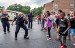 First Place | General News Allison Lee Isley, Winston-Salem Journal / Randolph Community College Rocky Mount Police Department Lt. Charles Williams, left, and Lt. George Robinson, right, cheer on Spo. Tony Taylor as he takes the spotlight during the dance-off with children from Cokey Apartments for National Night Out on Tuesday evening, Aug. 2, 2016 at Cokey Apartments in Rocky Mount, N.C.