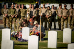 Honorable Mention | General News Andrew Craft, The Fayetteville Observer Tech. Sgt. Chris Shaub, left to right, Sibley's mother, Suzi Fernandez, and Sibley's girlfriend Hanna Broz kneel and comfort each other in front of Sgt. Forrest Sibley's grave on Friday, Aug. 26, 2016, on Naval Air Station Pensacola. Airmen of the 21st Special Tactics Squadron conducted high altitude high opening maritime insertion off the coast of Florida as part of a training exercise that will also honor last year's loss of Sgt. Sibley, an airman killed in Afghanistan.