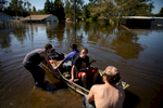 First Place | News Photo Story Andrew Craft, The Fayetteville ObserverTravis Odum, left to right, Carlos Gomez, Tony Ford prepare to go out in a boat to reclaim household items from their flooded home on Macon Street on Wednesday, Oct. 12, 2016, in Lumberton, N.C.