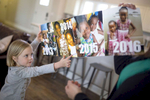 First Place | Feature Photo Story Madeline Gray, North State Journal Carina Coleman, 5, points to a timeline showing photos of her adopted sisters as the family waits for them to arrive from the Democratic Republic of the Congo. The family has had to wait over three years for the two sisters to be allowed to leave their home country and come to North Carolina.