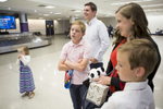 First Place | Feature Photo Story Madeline Gray, North State Journal (L to R) Members of the Coleman family Carina, Colin, Chad, Katie, and Gabriel wait at the Charlotte airport for Safi and Sifa, who have been legally adopted by the family for over three years, to arrive from the Democratic Republic of the Congo.