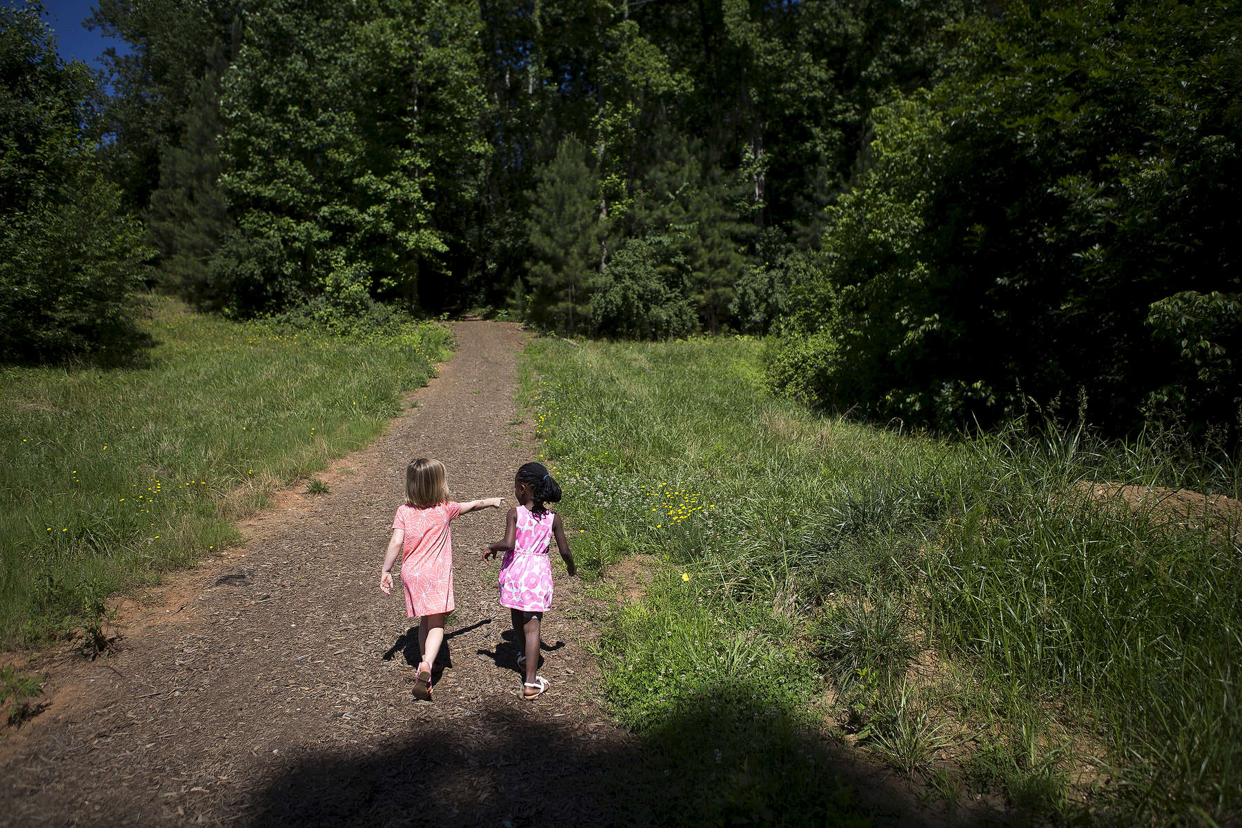 POY: Runner UpMadeline Gray, North State Journal Carina, 5, left, shows her new sister Sifa, 5, right, around the path near their house on Sifa's first full day in the United States with her adopted family.