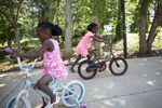 POY: Runner UpMadeline Gray, North State Journal Sisters Sifa, 5, left, and Safi, 6, right, ride bikes at their new home with the Coleman family in Charlotte, North Carolina. The Colemans have spent the last three years supporting the sisters in the Democratic Republic of the Congo while they waited for the girls to be allowed to come to the United States.