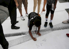 Sports POY: Runner UpEamon Queeney, North State Journal Nicholes Levy, 10, of Charlotte, signs the track after his brother Sidney, right, during the Coca-Cola 600 at Charlotte Motor Speedway, Sunday, May 29, 2016. Martin Truex Jr. made NASCAR history in his No. 78 Furniture Row Racing Toyota by leading more laps and more miles than any other driver in any race in NASCAR history while landing himself in Victory Lane.