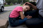 Aya lays on her father Ahmed's lap outside their family home in Toronto.