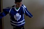 Moutayam puts on his Toronto Maple Leaf jersey in his room in his family home in Toronto.