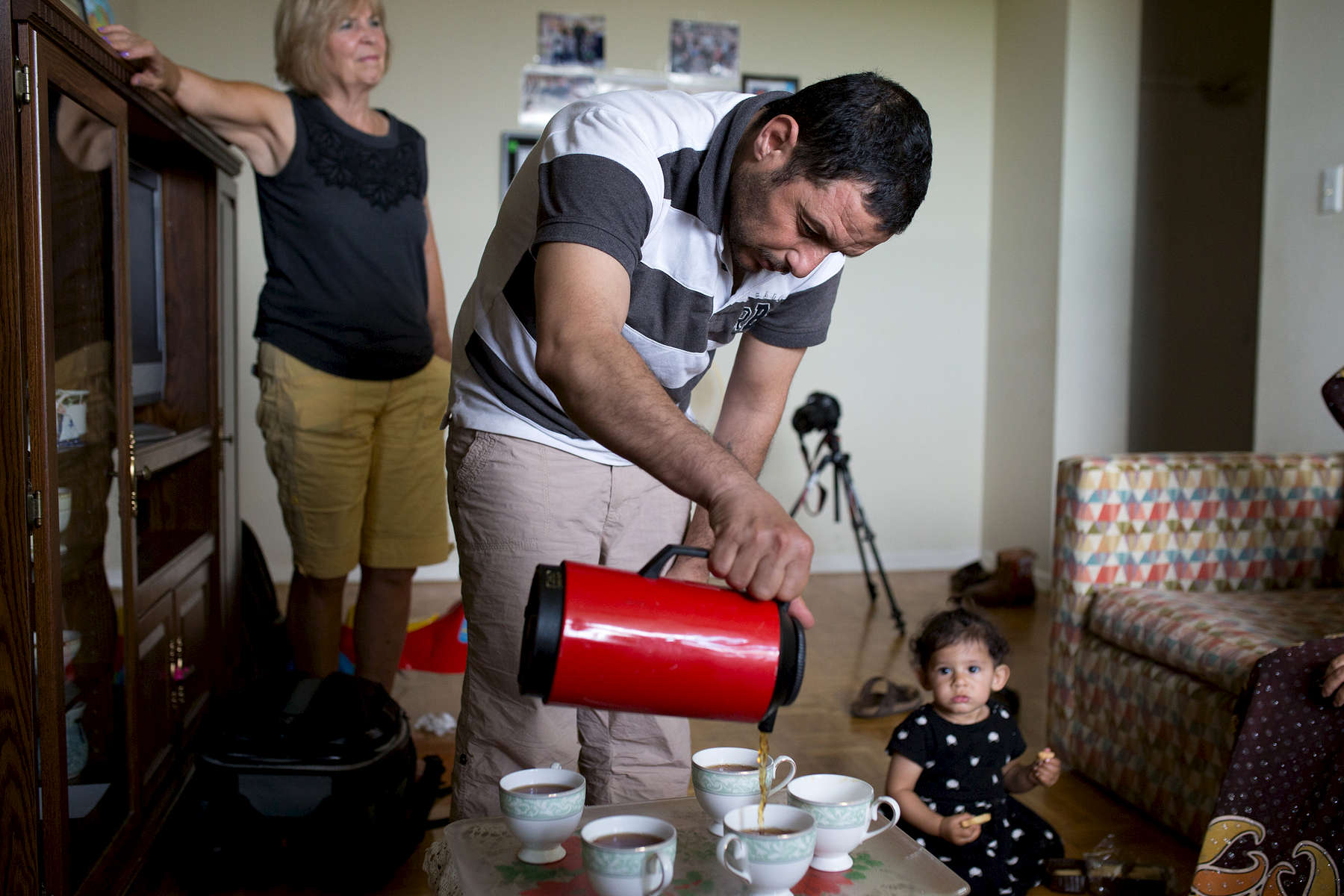 Mouhamed pours tea in his family home in Toronto.