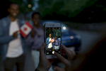 Catherine LeBlanc-Miller takes a photo of Yahya Adam and Mohamed Farah holding up a Canadian flag on a street in the Beaches neighbourhood of Toronto.