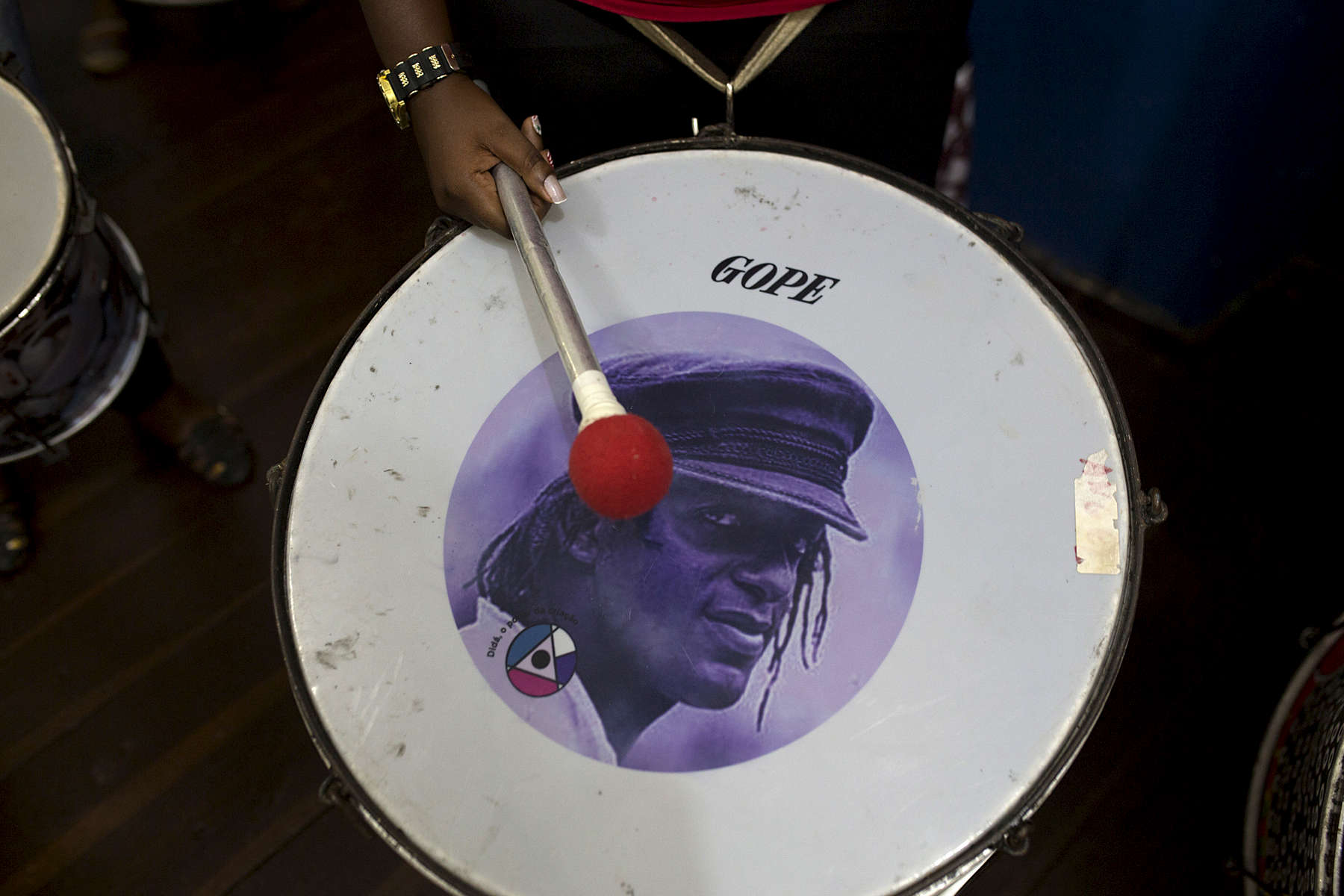 A Didá band member with a surdo drum, with the face of Didá founder Neguinho do Samba, at Project Didá in Salvador's historic neighborhood, Pelourinho.