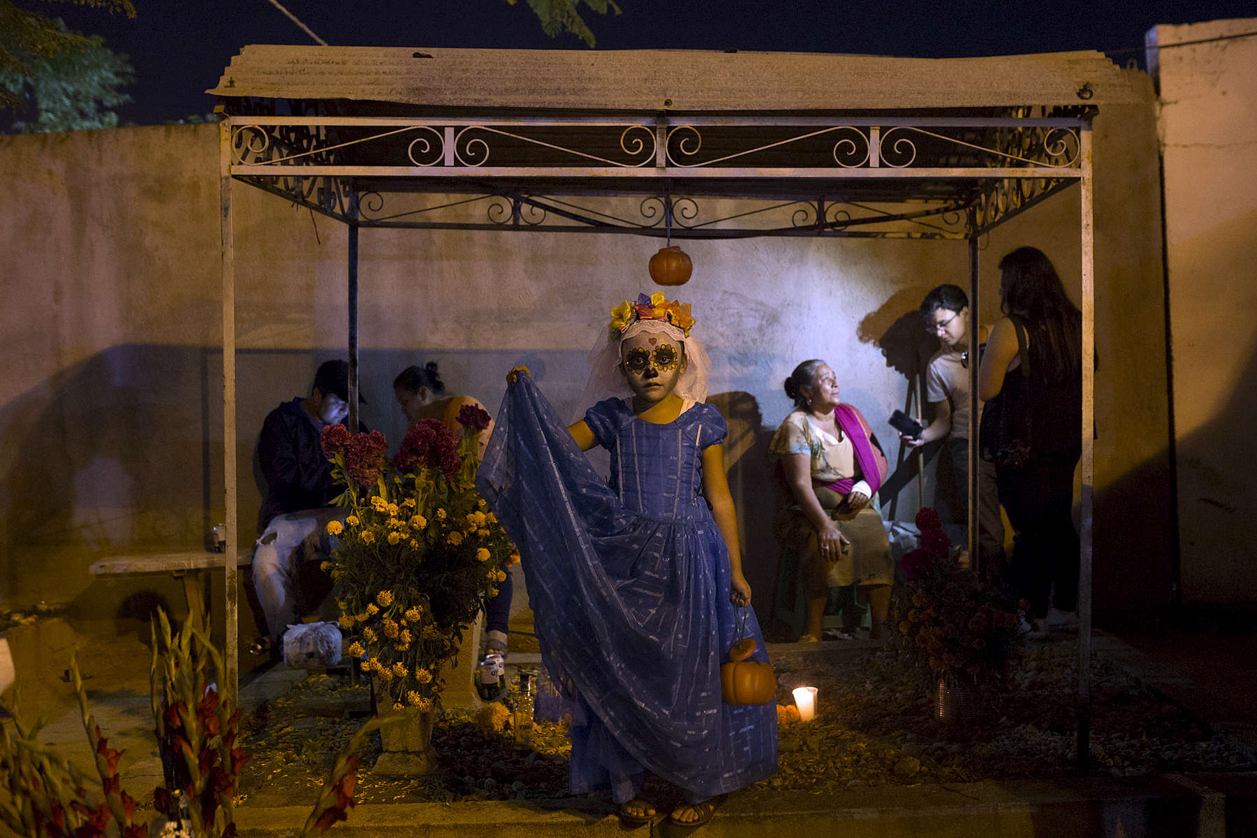 Margarita Jimenez stands on a grave in Panteon Viejo Xoxocotlán during Day of the Dead.