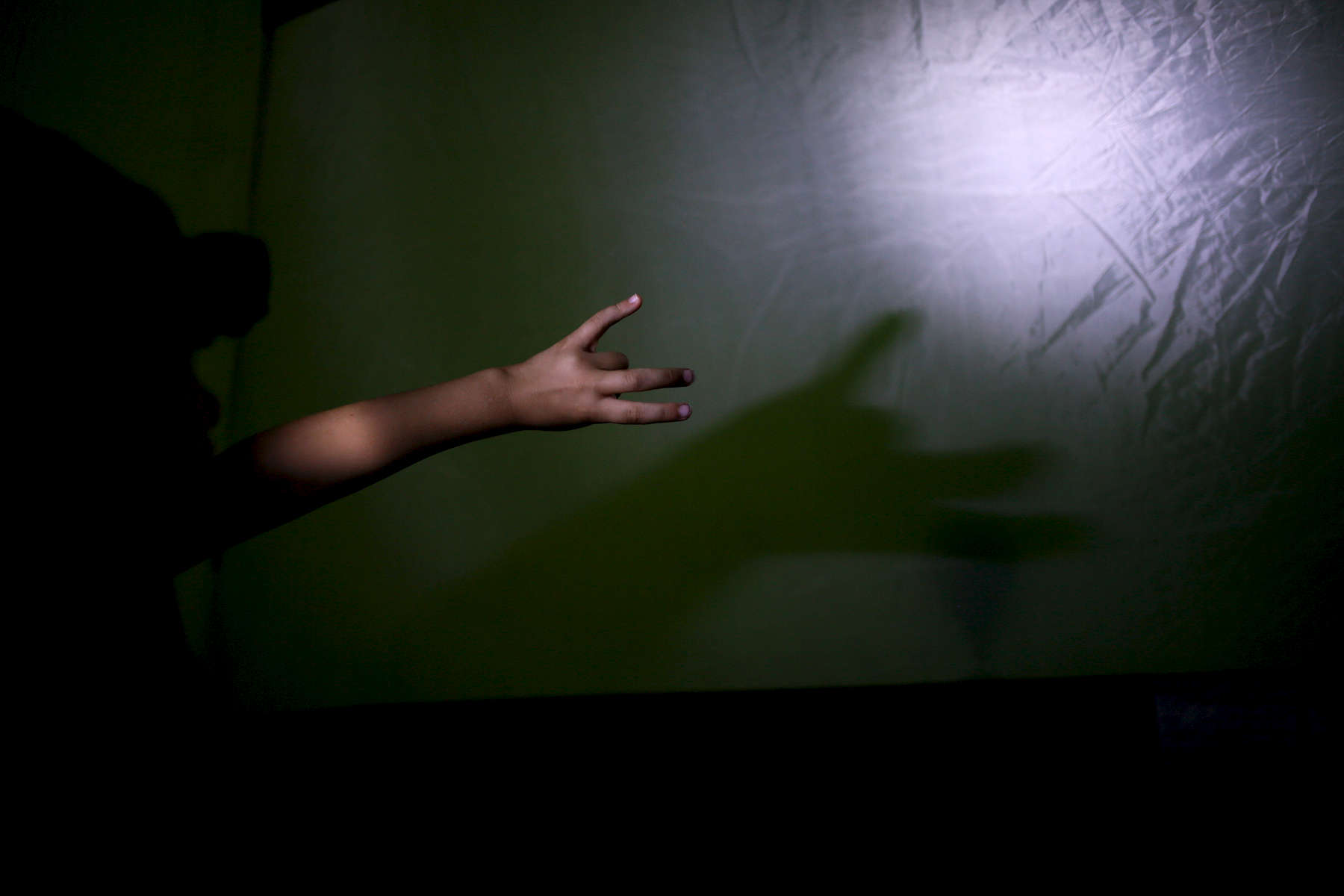Violet makes a shadow puppet from a flashlight.