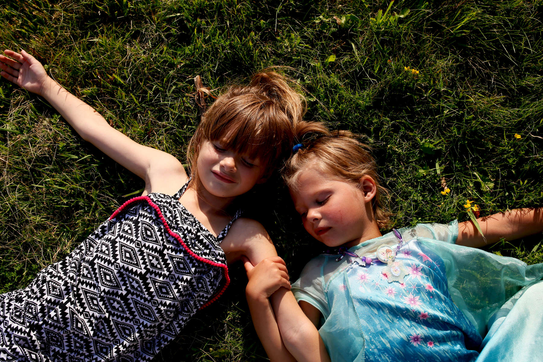 Lila and Violet lay on the grass after pretending to make snow angels on the front lawn of their grandmother's house.