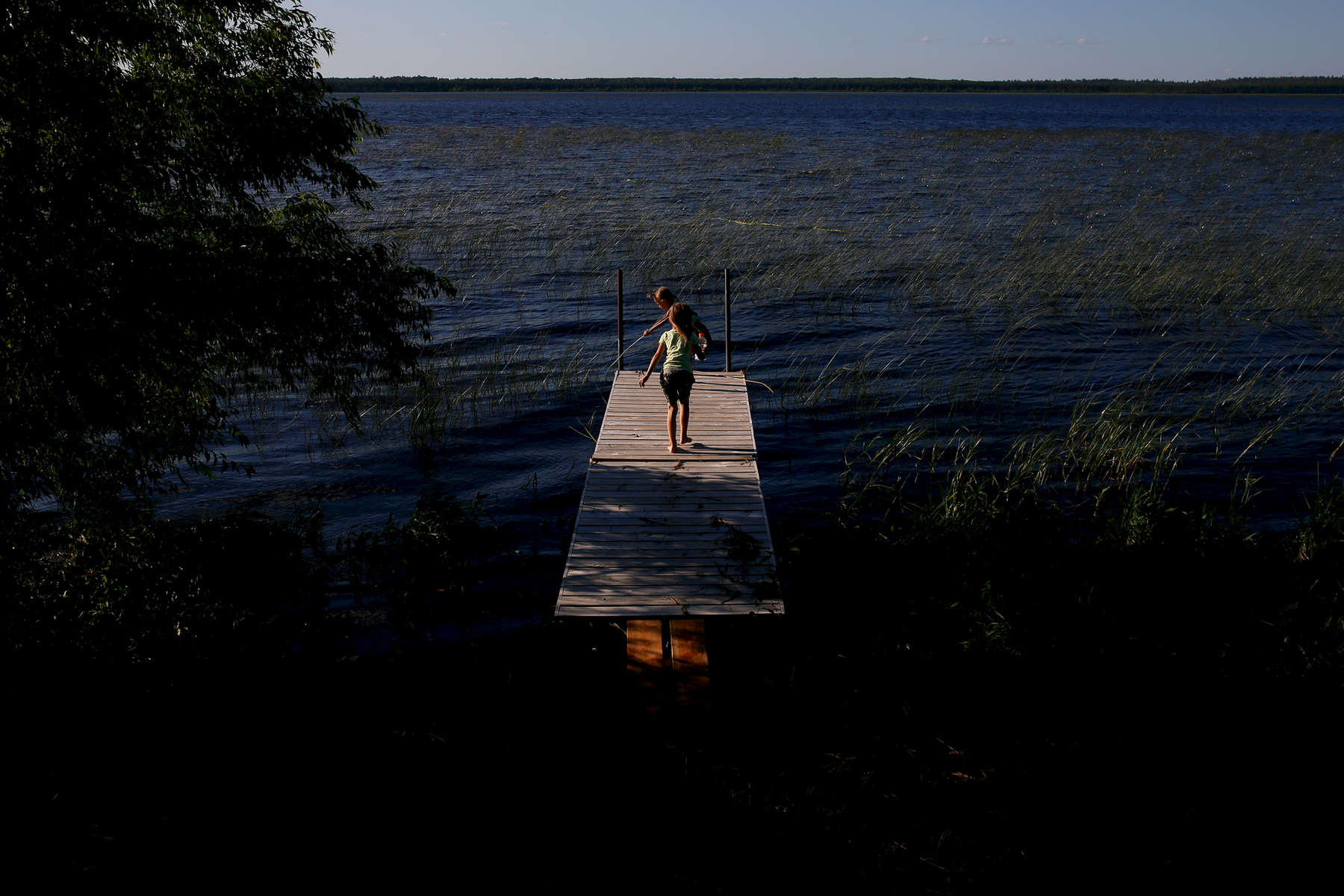Violet and Lila play on a dock on Nett Lake. The lake has wild rice and is considered sacred.
