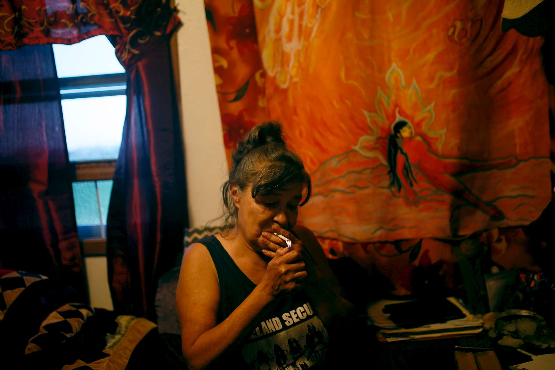 Heart Warrior lights a cigarette in her room. The space is decorated with paintings by both herself and her son Shaun.
