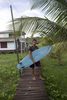 Ruan Maciel Borges, 19, shows off his wooden homemade surfboard, crafted from local Madeira trees. He made the board using the outline of a surfboard that a pro surfer gave their cousin Athieson Almeida Farias in 2017, then 16 years old, after seeing him ride the pororoca on a refrigerator door.