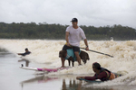 Ivan Moreira and Bono surf the tidal bore wave in between locals Valdinei Farias Mendes and Ruan Maciel Borges. Bono often likes to ride the board this way.