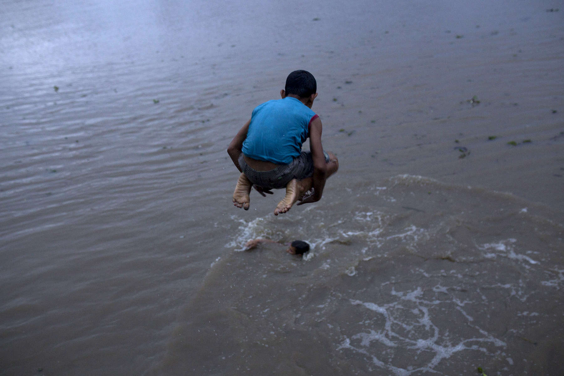 Davidson Ferreira Ferreira, 8, jumps into the Amazon River.