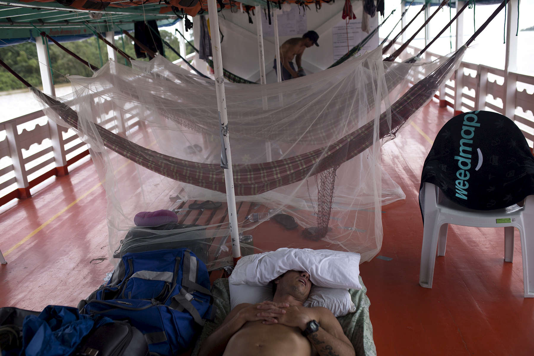 Surfer Ivan Moreira takes a nap on the boat. Serginho Laus gets into his hammock in the background.