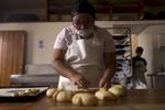 Norma Marcos Sánchez, 23, rolls the dough of the pan de muerto at Café Nuevo Mundo in Oaxaca City.