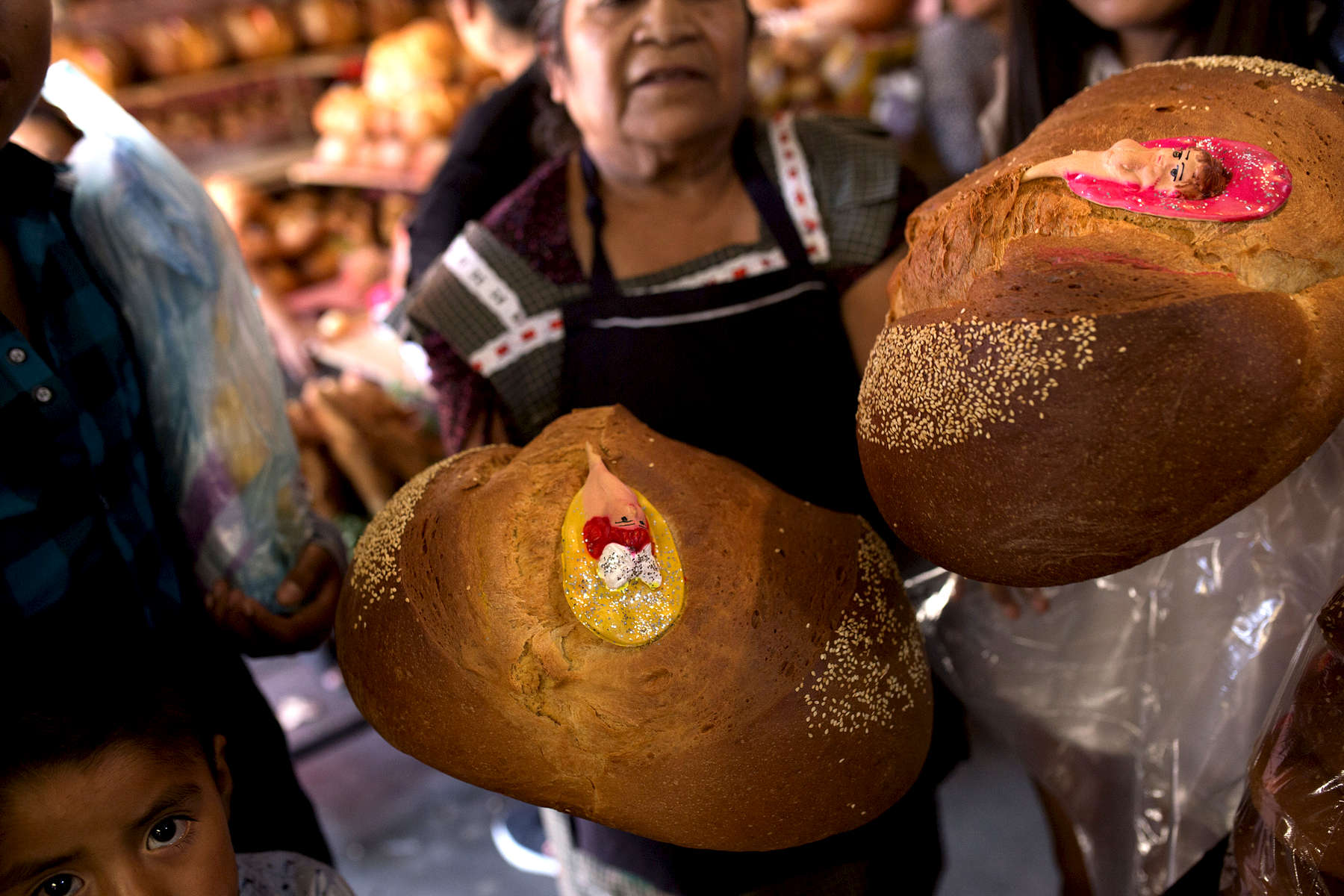 Ernesto Gonzalez (left) buys pan de muerto with his family from Soledad Martínez García (right) at Central de Abasto market in Oaxaca City.