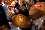 Ernesto Gonzalez (left) buys pan de muerto with his family from Soledad Martínez García (right) at Central de Abasto market in Oaxaca City.