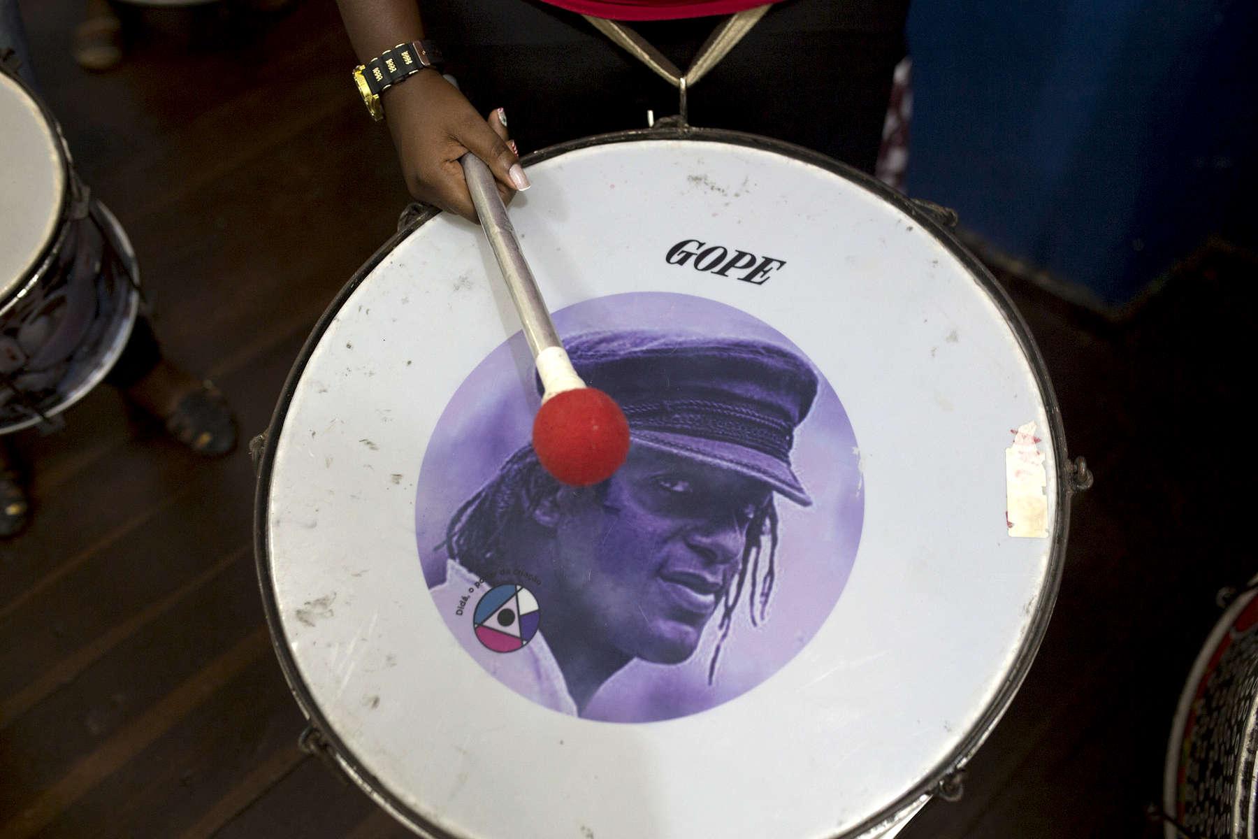 A Didá band member with a surdo drum, with the face of Didá founder Neguinho do Samba.