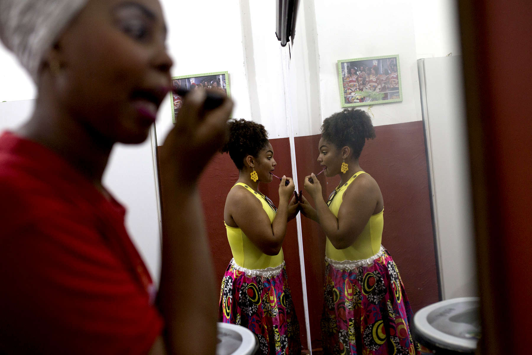 Carine Alves Teles dos Santos and Larissa Gabriele Rogerio put on makeup before a performance at Project Didá in Salvador's historic neighborhood, Pelourinho.