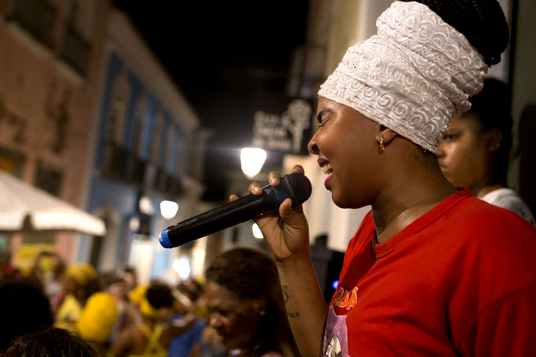 Carine Alves Teles dos Santos sings with the Didá band on the street outside Project Didá in Salvador's historic neighborhood, Pelourinho.