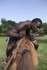 Dee Davis checks out his horse at the trail ride in Calvert, Texas.