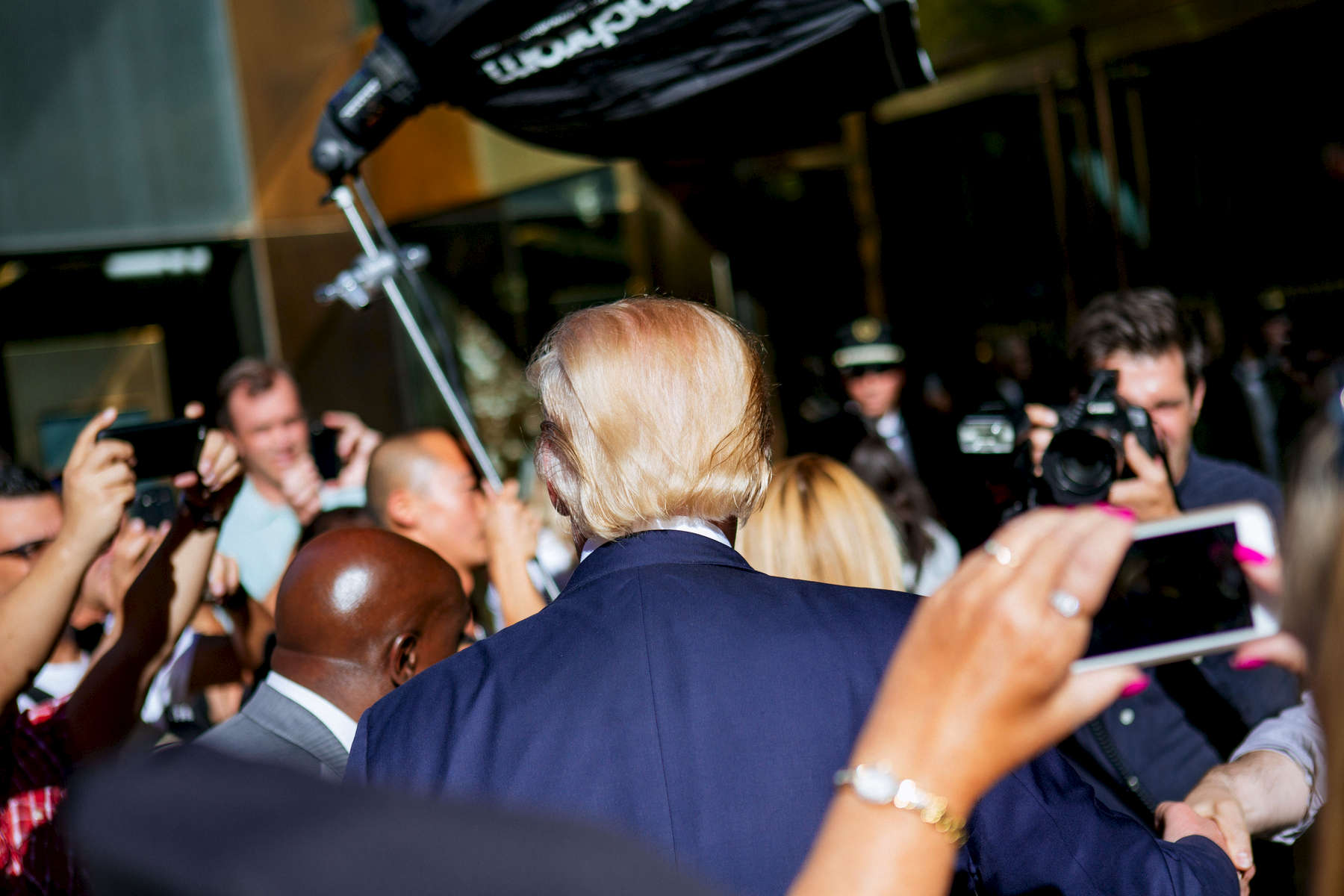 U.S. Presidential Candidate Donald Trump waves to onlookers after emerging briefly from Trump Tower dugong photo shoot Thursday, Sept. 24, 2015, in New York . (AP Photo/Kevin Hagen)