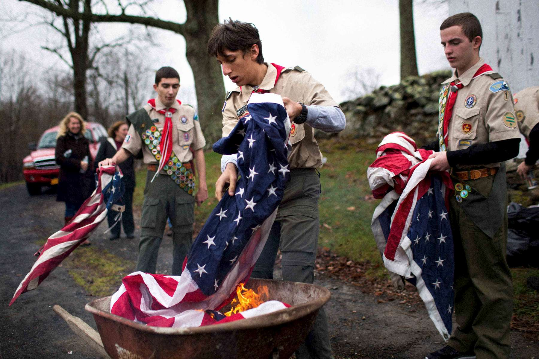 North Salem, NY - November 9, 2015: North Salem Troop 1 Boy Scouts Matthew Posa, 17, at left, Mason Goodman, 16, and David Posa, 15, burn flags as part of a flag retirement ceremony at the June Cemetery in North Salem, NY Wednesday Nov. 11, 2015. Lois Colley, 83, a Westchester County socialite, was murdered Monday night at her home in North Salem. CREDIT: Kevin Hagen for The New York Times
