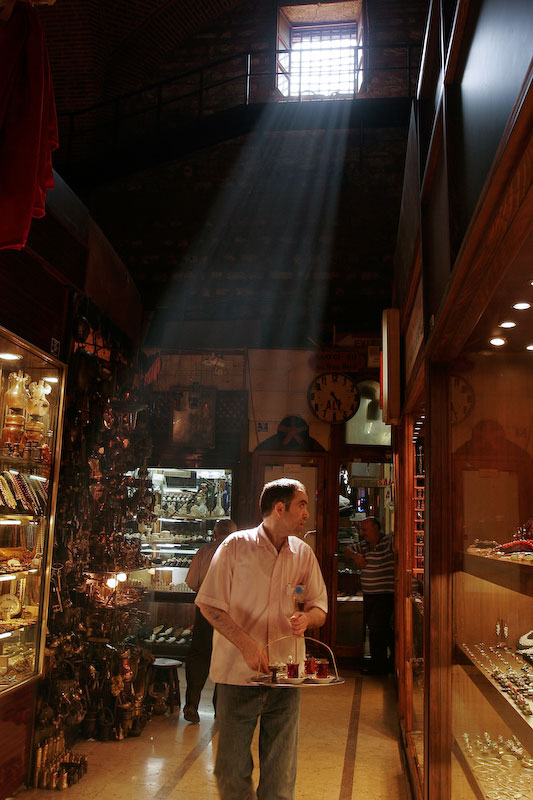 A man walks around an indoor market selling tea in Istanbul, Turkey.