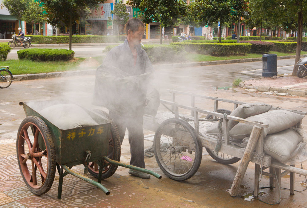 A construction worker loads bags of cement onto carts in Wuyuan City, China. Richard U. Light Foundation.
