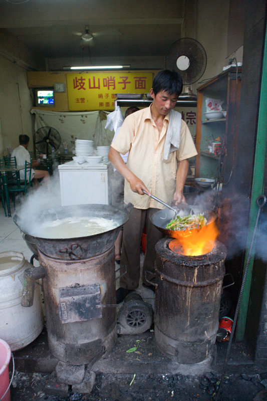 A man cooks noodles in his restaurant in Xian, China. Richard U. Light Foundation.